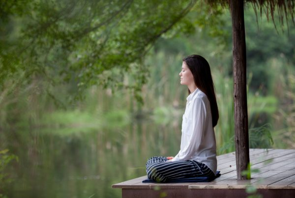 woman-meditating-nature-lake-trees