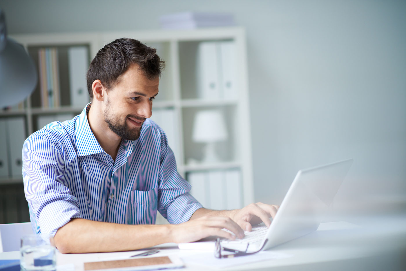 spanish-to-english-translation-human-translation-services-man-laptop-smiling-typing-sitting-at-desk