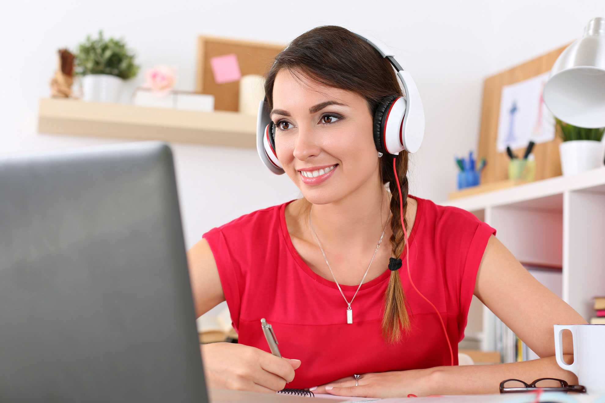 online-trainings-young-woman-headphones-laptop-listening-smiling-home-office